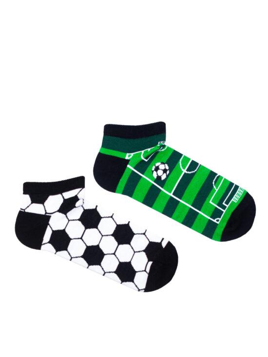 Kolorowe stopki męskie piłka nożna, dwie różne na jednej w motyw piłki z czarnymi łatami na białym tle , na drugiej zielona w kształcie murawy z białką oraz liniami boiska z czarnymi ścigaczami