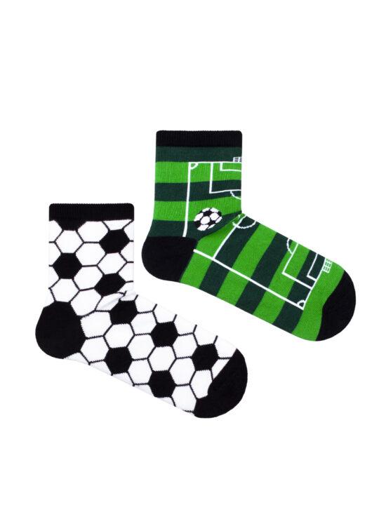 Skarpetki dziecięce, dwie różne z czarnym wykończeniem, jedna z motywem piłki w kolorze białym i czarnym na drugiej boisko z zielonymi paskami