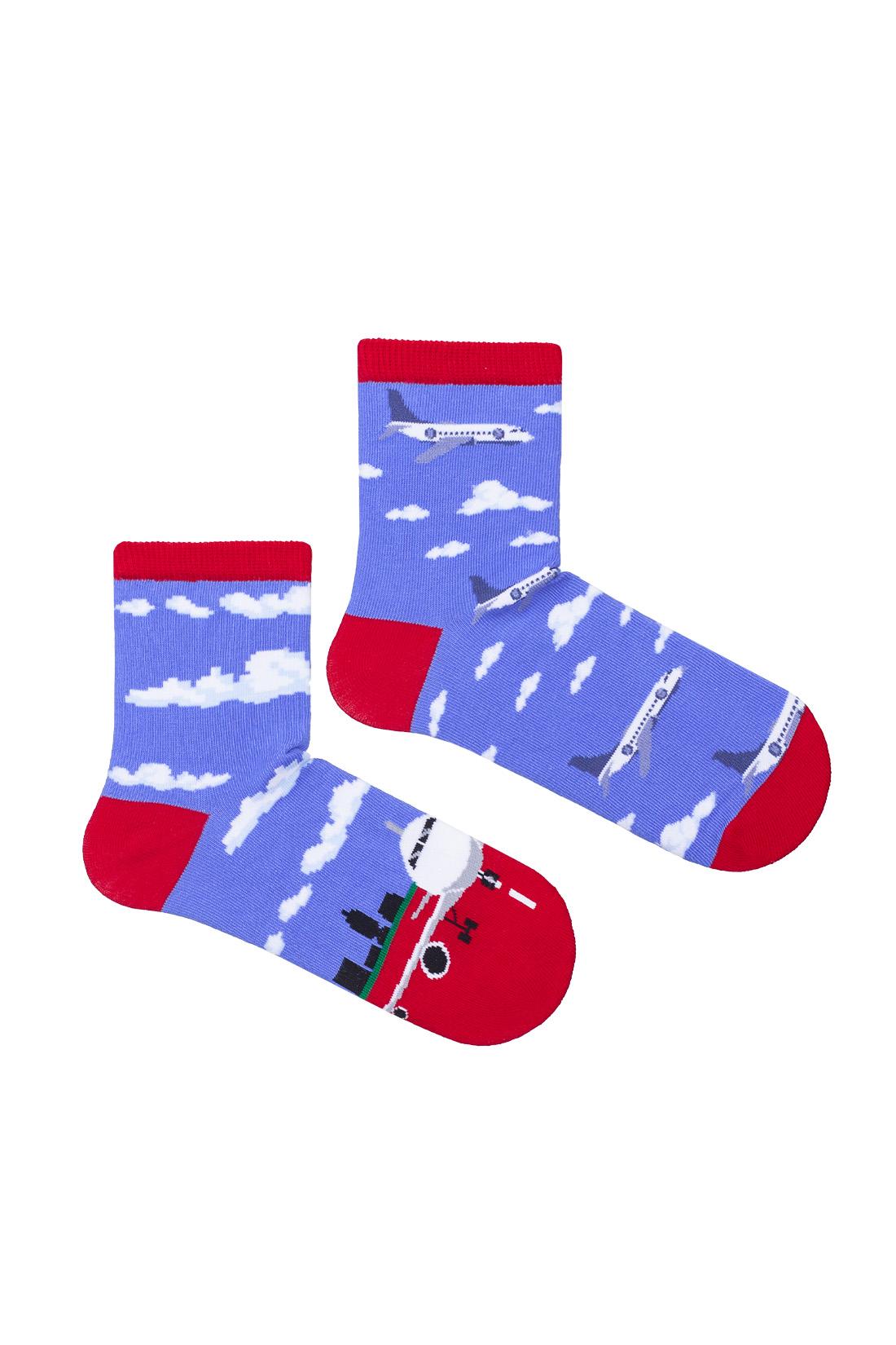 Kolorowe skarpetki dziecięce niebieskie z czerwonym wykończeniem, dwie różne na jednej duży samolot na pasie startowym w otoczeniu budynków ,trawy i chmur, na drugiej samoloty w powietrzu w otoczeniu chmur