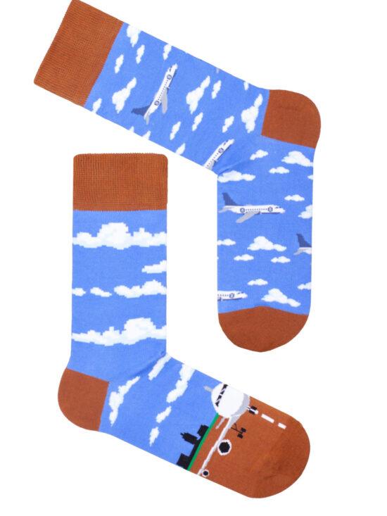 Kolorowe skarpetki męskie, dwie różne. Na niebieskim tle z brązowym wykończeniem. Na jednej duży samolot na pasie startowym, na drugim samoloty wśród chmur
