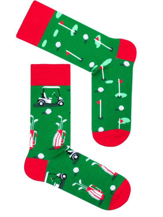 Kolorowe skarpetki męskie zielone z czerwonym wykończeniem, dwie różne na jednej pole golfowe z dołkami i piłeczkami, na drugiej meleks,plecak z kijami i piłeczki
