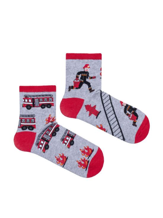 Kolorowe skarpetki dziecięce, dwie rózne na jednej wozy strażackie i płomienie na drugiej drabina strażak i płomienie wszystko na szarym tle z czerwonym wykończeniem