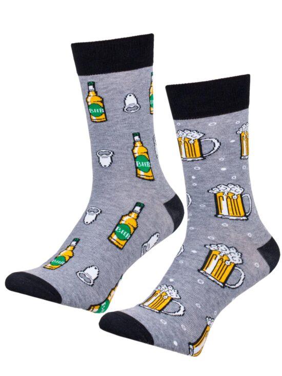 Kolorowe skarpetki męskie , dwie różne na jednej kufle z piwem an drugiej piwo w butelce z otwieraczem, na szarym tle z czarnym wykończeniem